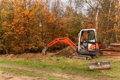 在建造场所的微型挖掘机 一个家庭房子的建筑在森林附近的 库存照片