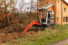 在建造场所的微型挖掘机 一个家庭房子的建筑在森林附近的 库存图片