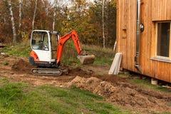 在建造场所的微型挖掘机 一个家庭房子的建筑在森林附近的 图库摄影