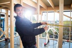 在建造场所的木匠测量的木头 免版税库存图片