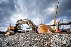 在建造场所的耐用工业挖掘机装货石渣 建筑工地细节  库存图片
