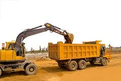 在建造场所,土壤转动挖掘机和翻斗车有白色背景,轮子挖掘机 库存图片