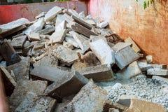 在建造场所,家庭整修附近的被装载的大型垃圾桶 免版税图库摄影