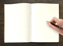 在开放书的手文字在桌上 免版税库存图片