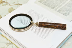 在开放书的放大镜 免版税库存图片