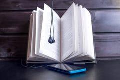 在开放书的耳机与音频使用的电话 免版税库存图片