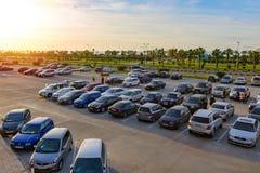 在开放停车处的很多汽车,人们在棕榈树背景中走,绿色树,并且太阳发光 免版税库存照片