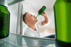 在开放冰箱前面的人饮用的啤酒 库存图片