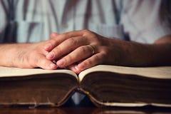 在开放圣经的男性手 免版税库存图片