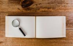 在开放旧书空白的放大镜 免版税库存照片