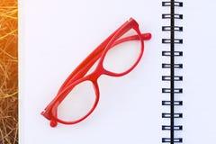 在开放空白的笔记本的红色玻璃在领域 免版税图库摄影