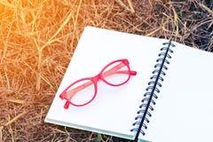 在开放空白的笔记本的红色玻璃 免版税图库摄影