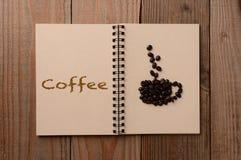 在开放笔记本的咖啡豆 免版税图库摄影