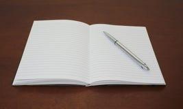 在开放笔记本纸的笔  免版税库存图片