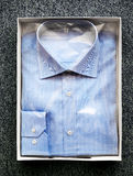 在开放箱子的被折叠的蓝色按钮下来衬衣 图库摄影