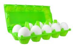 在开放绿色塑料包裹的十二个白鸡蛋在白色背景侧视图的被隔绝的关闭 免版税图库摄影