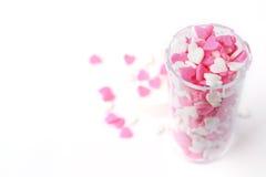 洒在开放药瓶的心脏,爱是医学 免版税库存照片