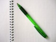 在开放螺纹笔记本的绿色铅笔 库存图片