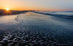 在开普梅, NJ,作为低潮的海滩的日出starburst横跨沙子流动 免版税库存照片