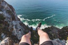 在开普角供以人员坐峭壁边缘在海洋的 免版税库存图片