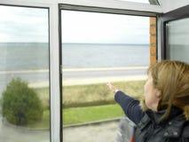 在开窗口附近的妇女 免版税库存图片