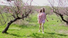 在开花的树庭院里跑桃红色礼服的金发碧眼的女人 股票录像
