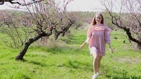 在开花的树庭院里跑桃红色礼服的金发碧眼的女人 影视素材