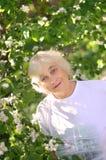 在开花的树附近的一名年长妇女 免版税库存照片