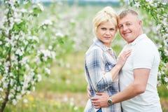 在开花苹果树的微笑的成人夫妇 免版税库存照片