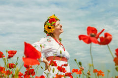 在开花领域中的愉快的微笑的乌克兰妇女 库存图片