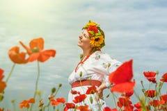 在开花领域中的愉快的微笑的乌克兰妇女 免版税库存照片