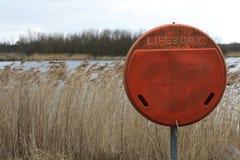 在开阔水域和芦苇旁边的Lifebuoy 免版税图库摄影