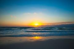 在异乎寻常的海滩的惊人的五颜六色的日落 库存照片