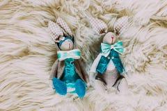 在弓领带的两个逗人喜爱的玩具兔宝宝在白色背景 免版税库存图片