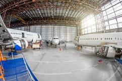 在引擎和机体修理维护的三台客机在机场飞机棚 免版税库存图片