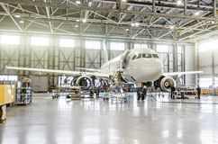 在引擎和机体修理维护的客机在机场飞机棚 免版税库存图片