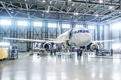 在引擎维护的乘客飞机和机体在机场飞机棚检查修理 库存照片