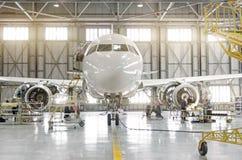 在引擎被拆卸的引擎刀片和机体修理维护的客机在机场飞机棚 库存图片