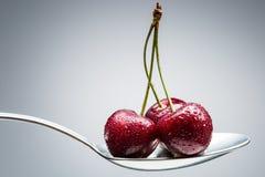 在弯曲的匙子的樱桃 图库摄影