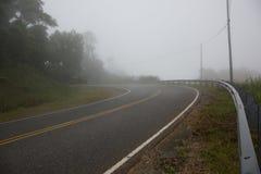 在弯曲的路的大雾使行车条件危险 免版税库存图片