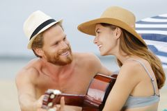 在弹吉他的海滩的愉快的年轻夫妇 免版税库存图片