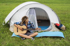 在弹吉他的帐篷附近的十几岁的女孩 免版税库存图片