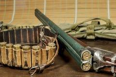 在弹药筒箱子旁边的老双筒猎枪 免版税库存照片