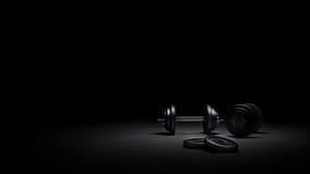 在强的剧烈的光下的健身房重量在blackbackground 库存照片