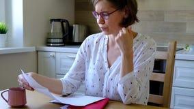 在强调的票据 看她的财政债务的Unpset妇女在厨房里 影视素材