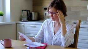在强调的票据 看她的财政债务的Unpset妇女在厨房里 股票录像