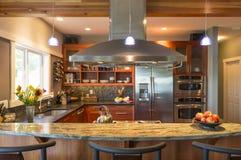 在当代高级家庭厨房内部的早餐吧台与花岗岩工作台面、出气孔敞篷和口音照明设备 免版税图库摄影