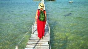 在录影的两个框架 一件长的红色礼服的妇女在沿大海的一个码头走 越南 的妇女 股票录像