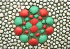 在形成一朵红色和绿色花的墙壁上的被绘的贝壳 免版税库存照片