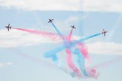 在形成的四架鹰T1喷气机与在飞行表演的彩色烟幕 库存照片